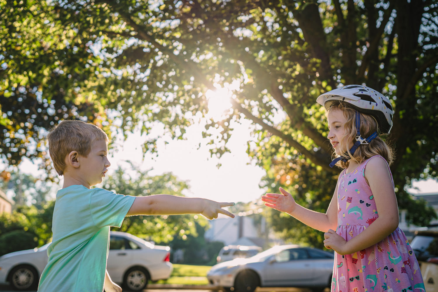 Siblings play rock, paper, scissors in their front yard.