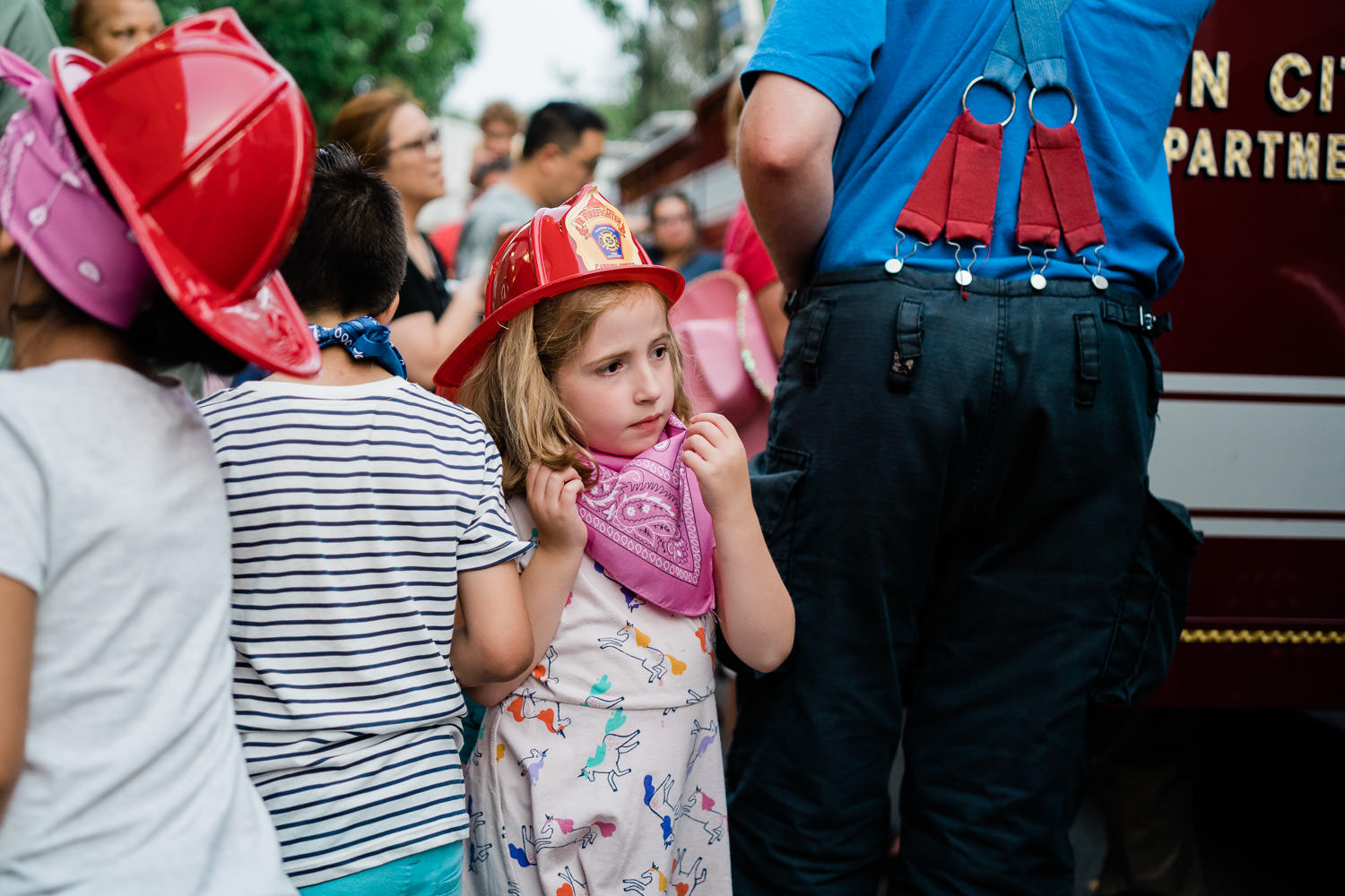 A little girl wanders through a crowd wearing a fire hat.