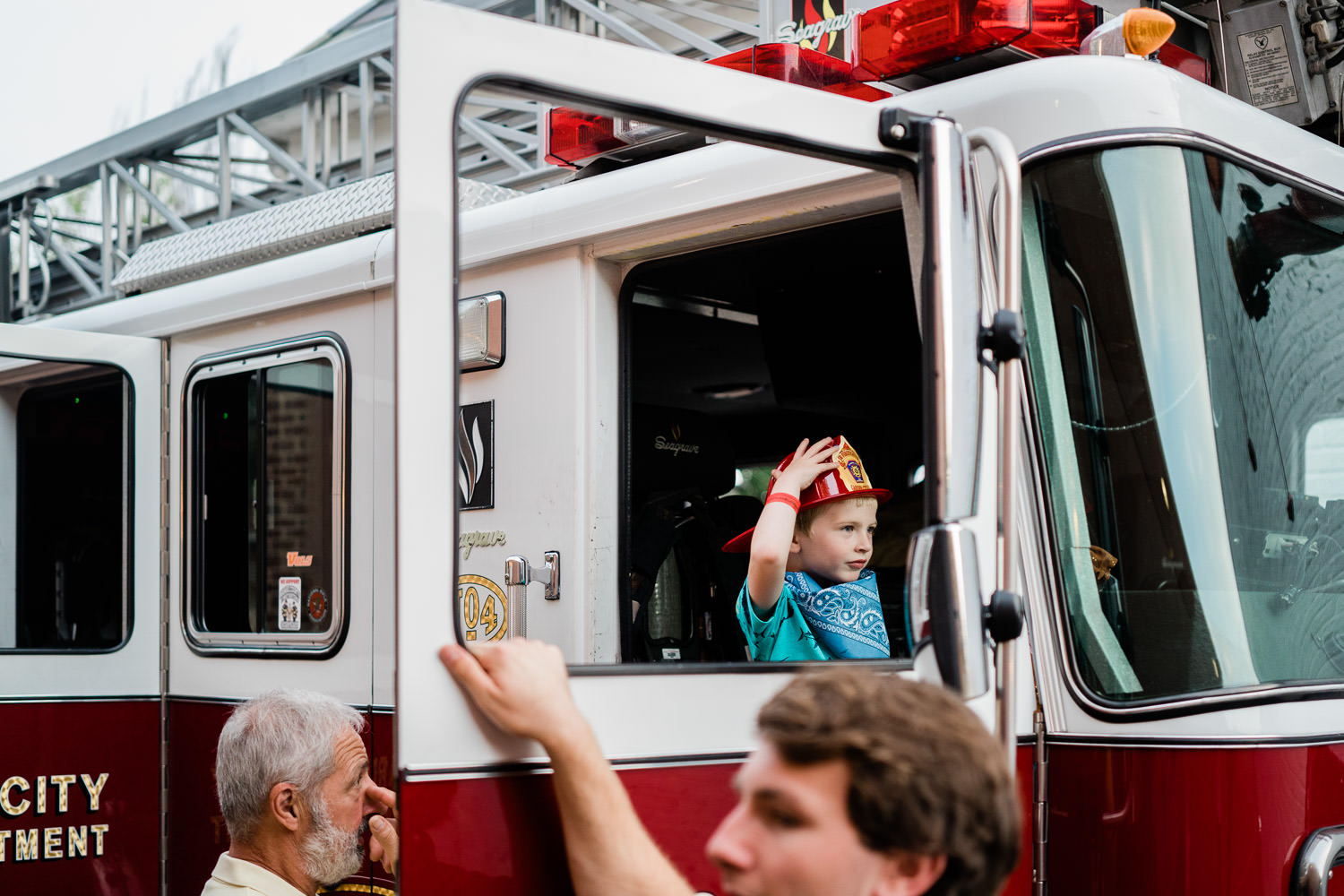 A little boy explores a fire truck.