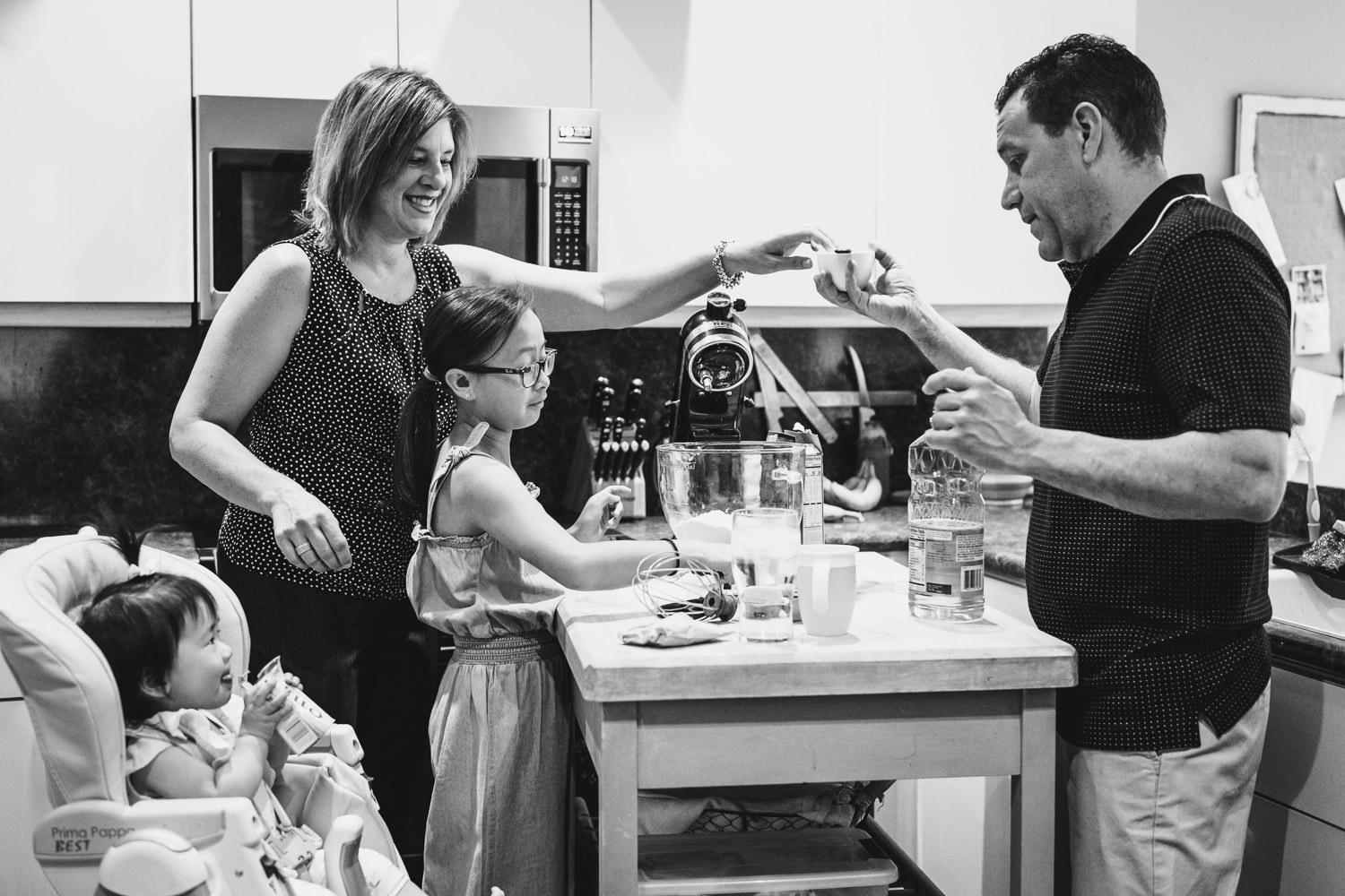 A family bakes a cake in their kitchen.