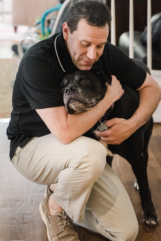 A man hugs his dog.