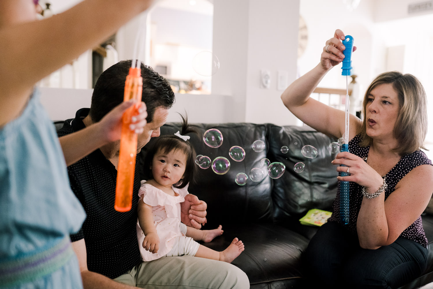 A family blows bubbles together.
