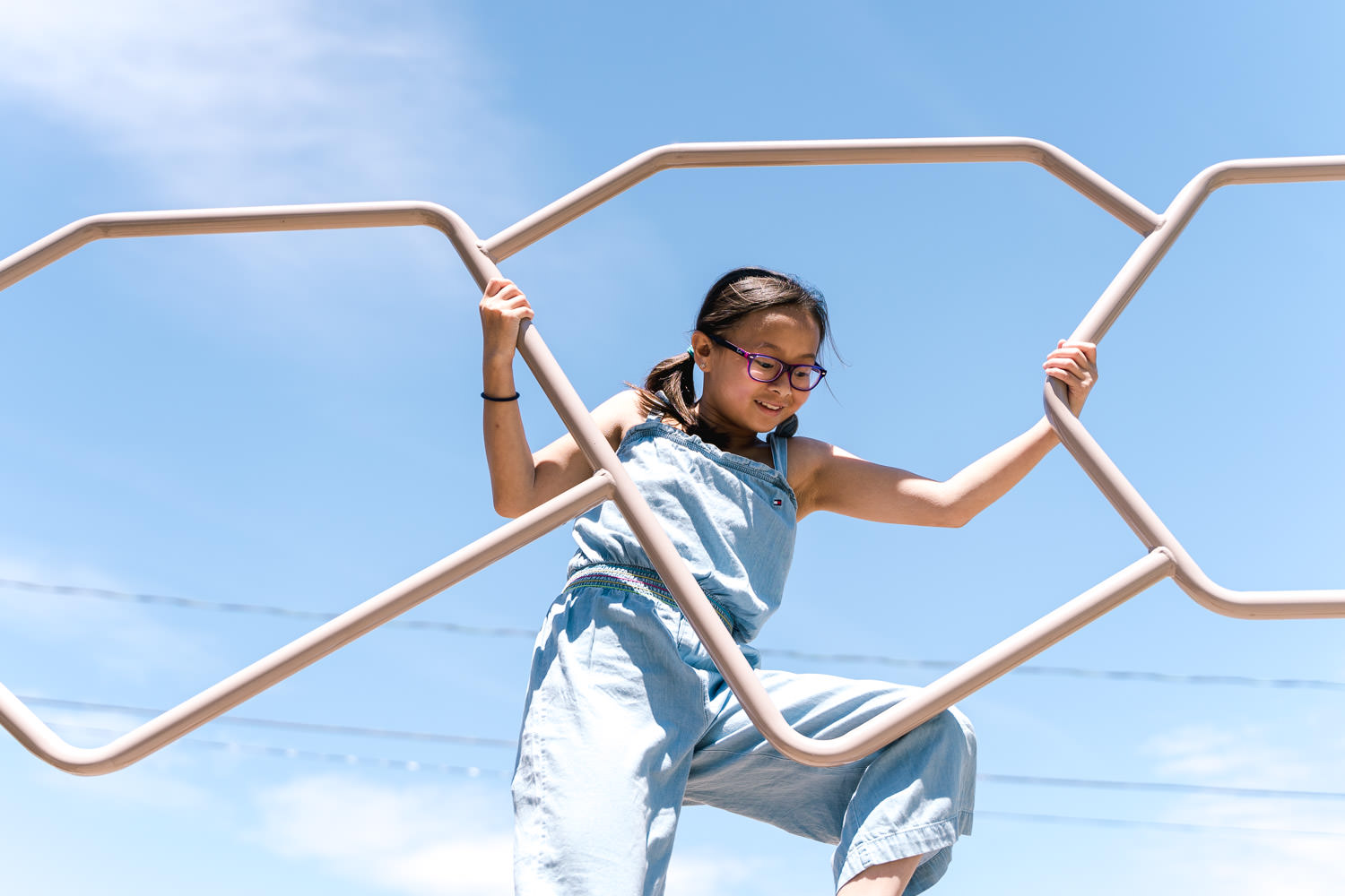 A young girl climbs a playground structure.