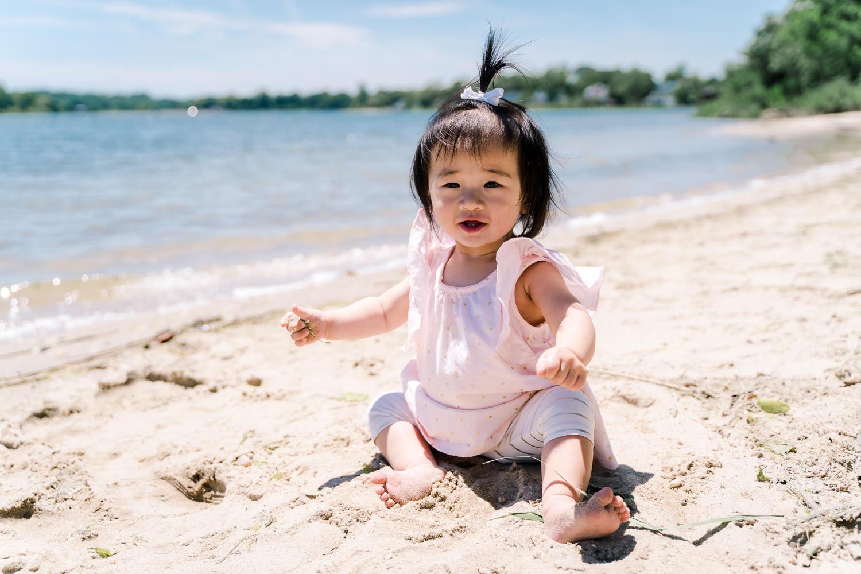 A little girl sits on the beach.