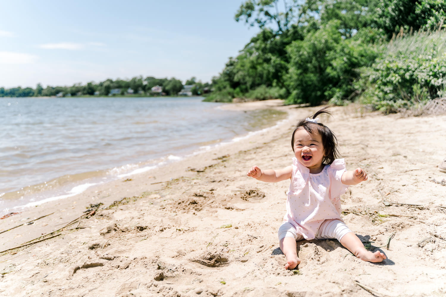 A baby girl sits near the water at the beach.