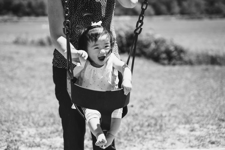 A little girl on a swing.