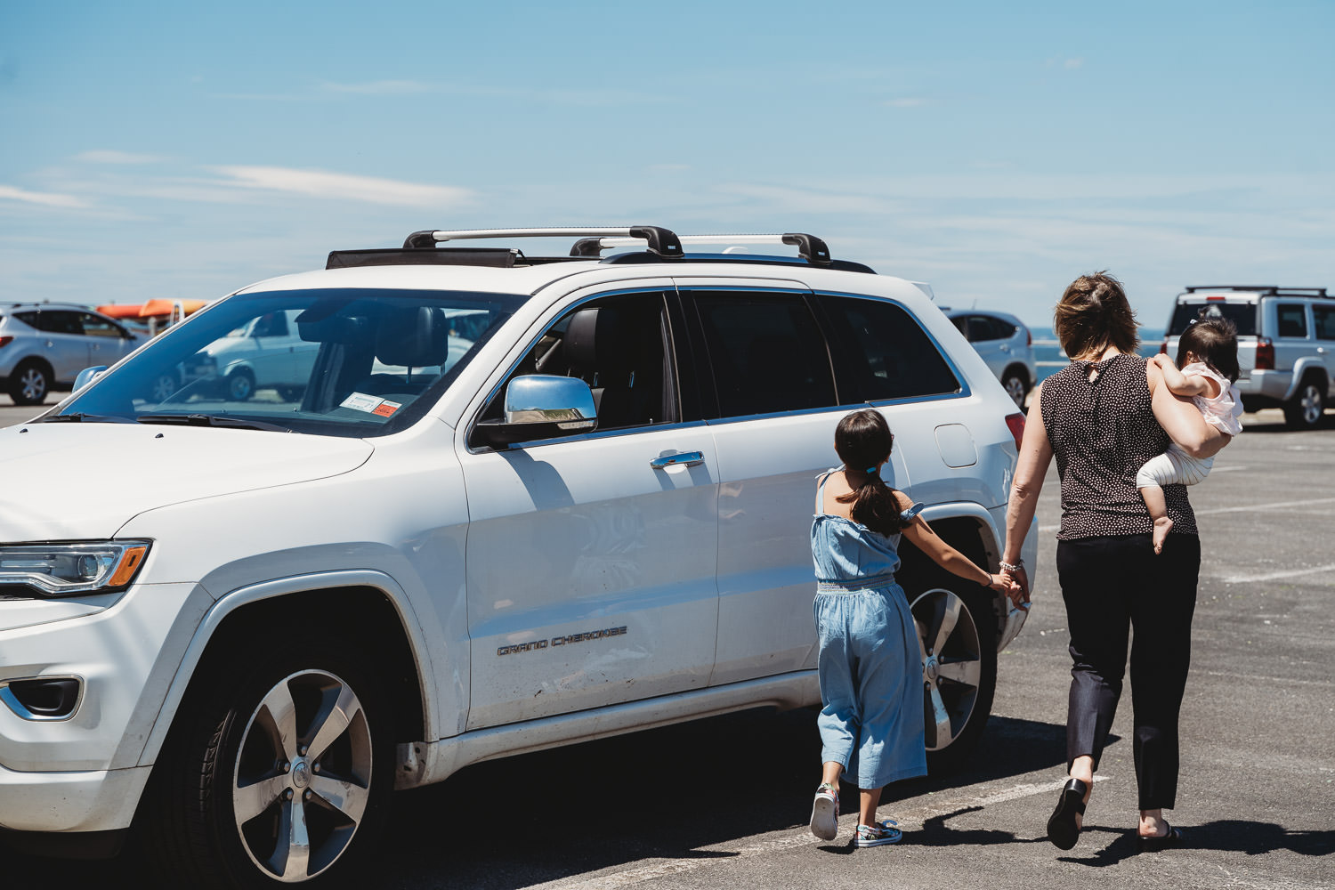 A mother walks back to her car with her two daughters.