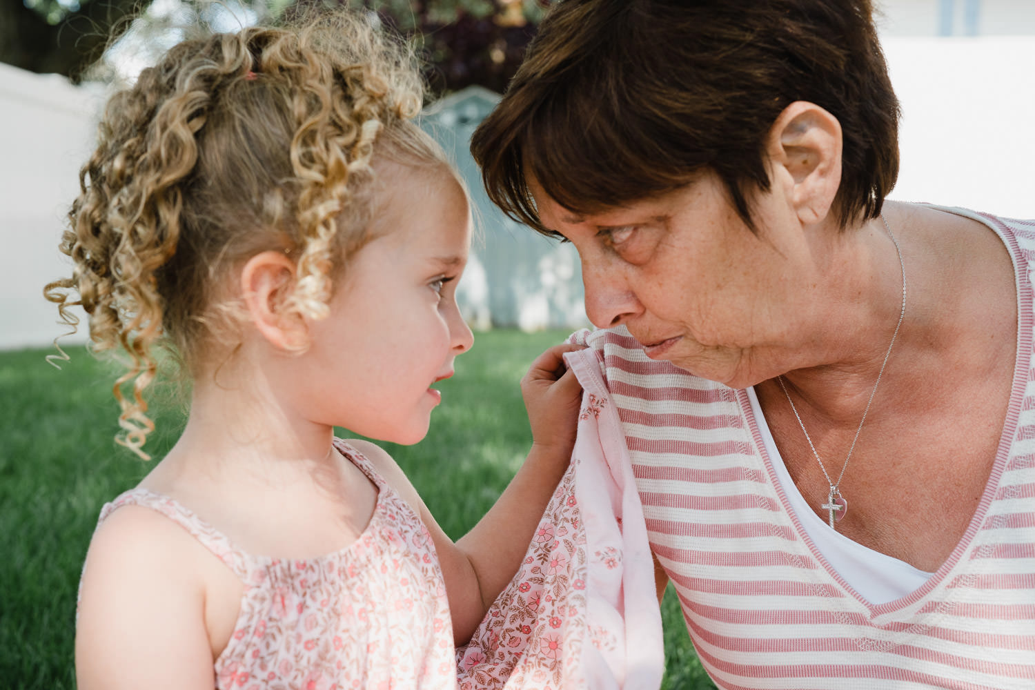A grandmother and granddaughter look in each others' eyes.