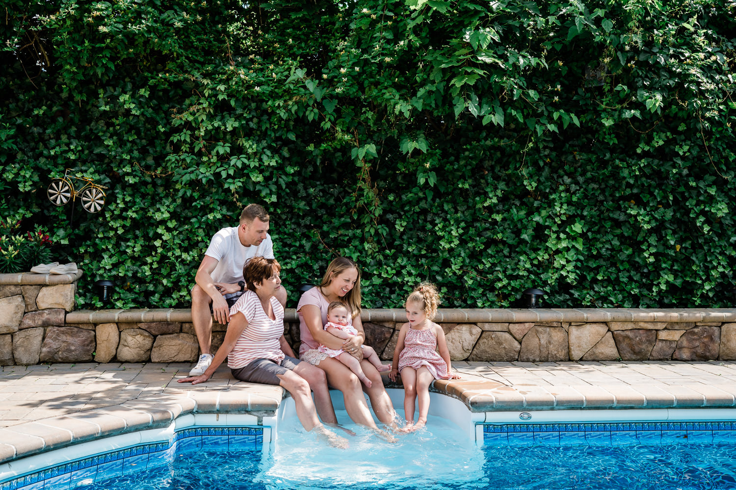 A family gathers around the pool.