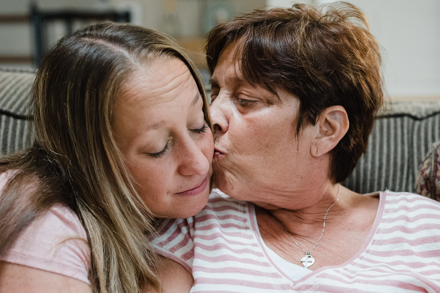 A mother kisses her daughter.