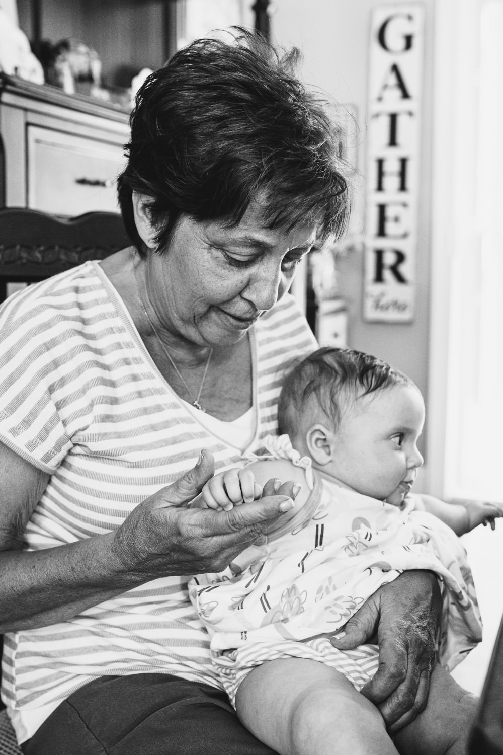 A grandmother looks at her granddaughter's hands.