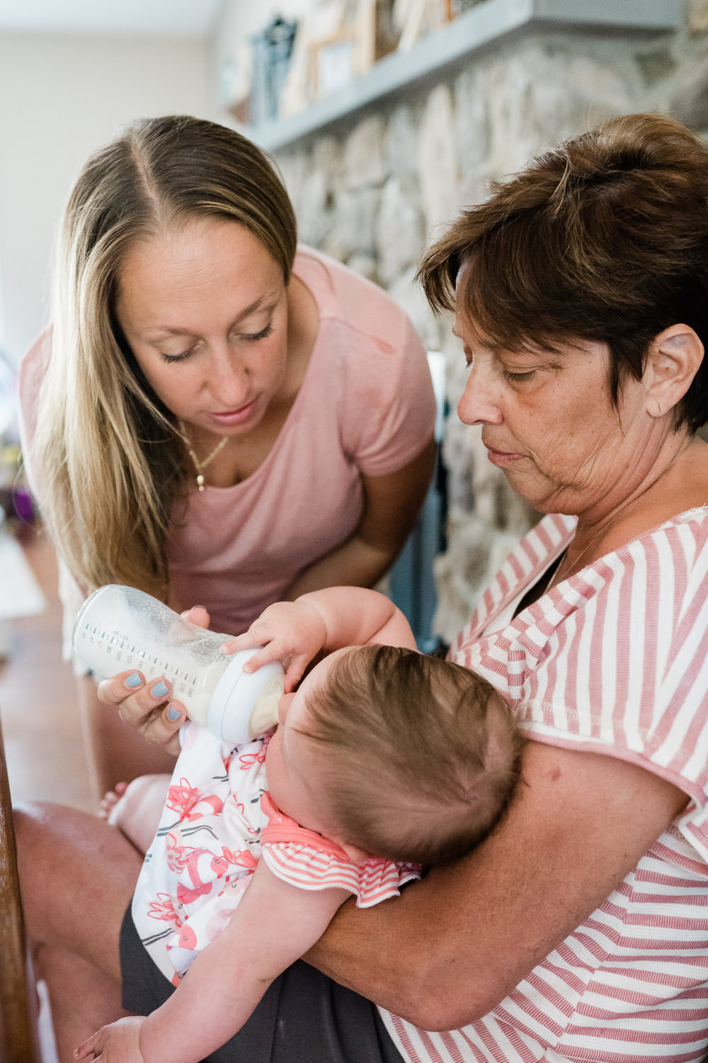 A mother and grandmother feed a baby.
