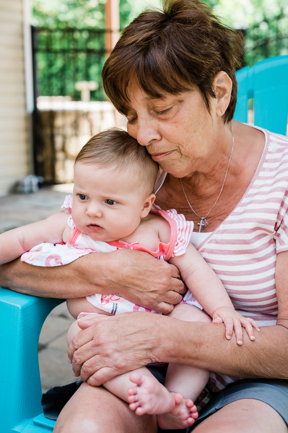 A grandmother holds her granddaughter.