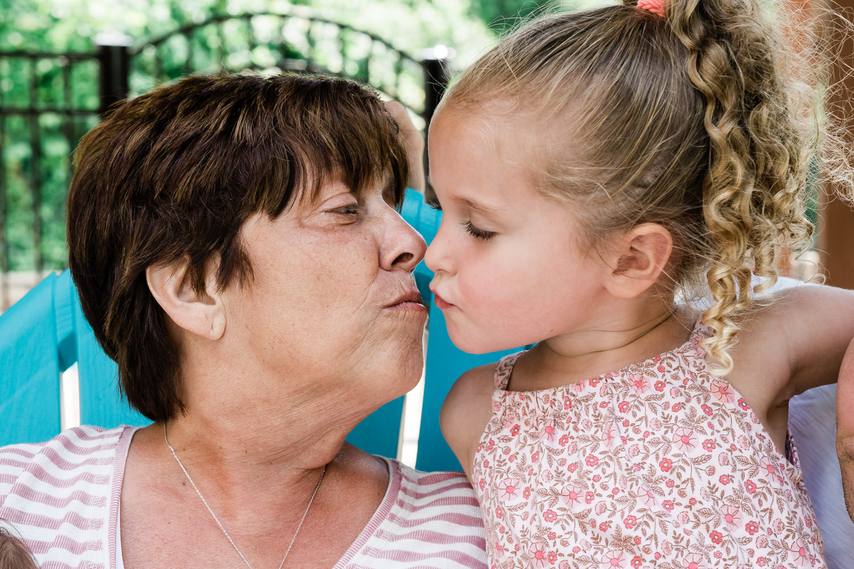 A grandmother kisses her granddaughter.