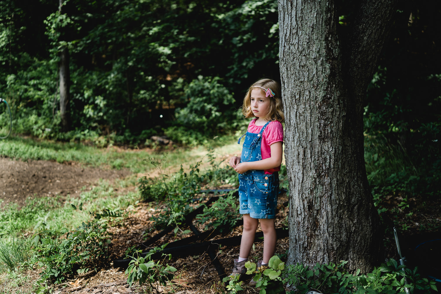A little girl stands by a tree at Restoration Farm.