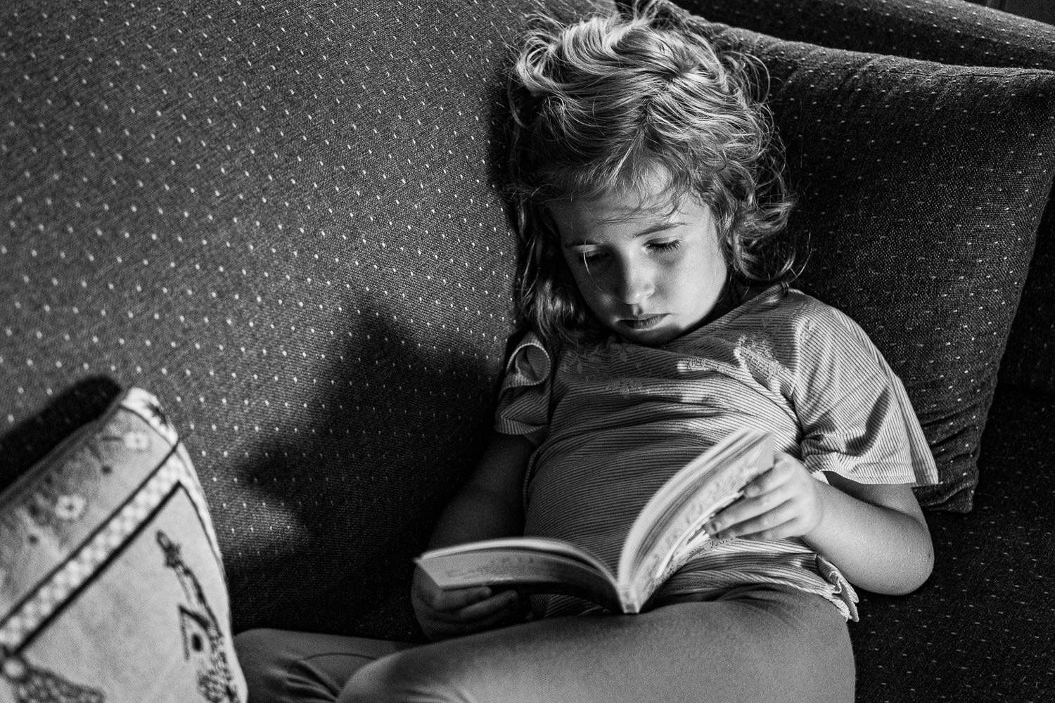 A little girl reads a book on a couch.