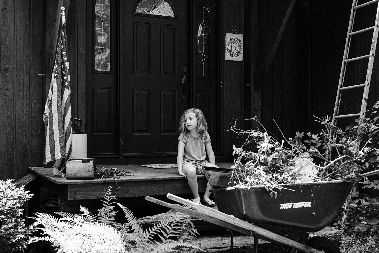 A little girl sits on a front porch.
