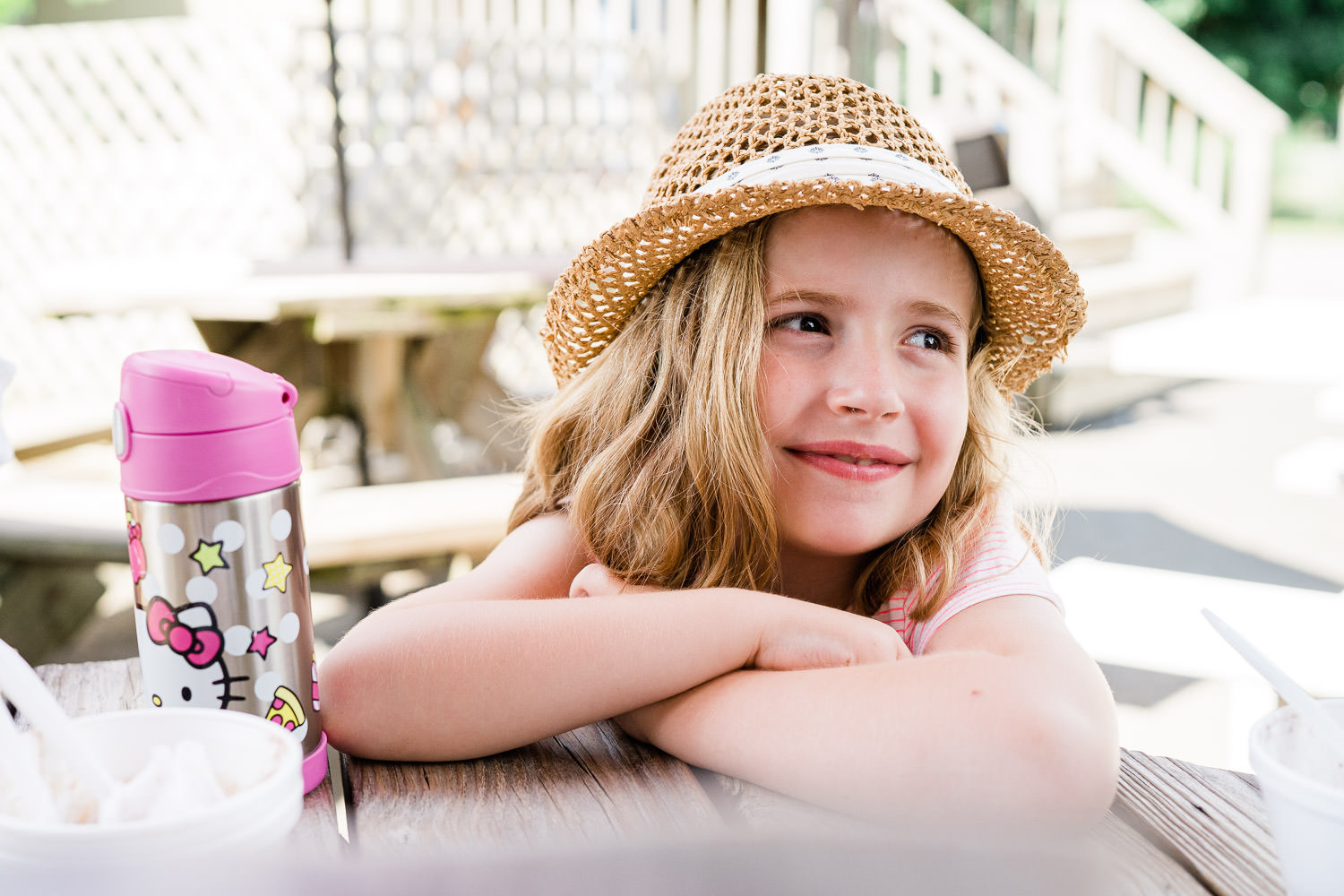 A little girl smiles at a picnic table.