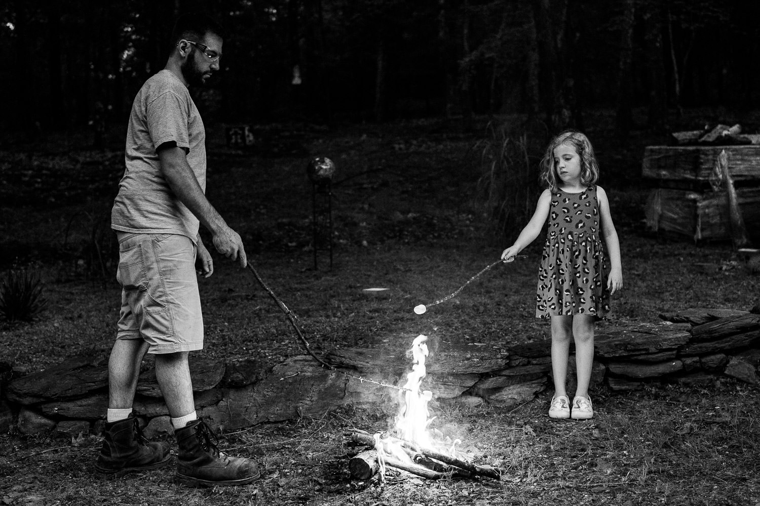 A father and daughter roast marshmallows.