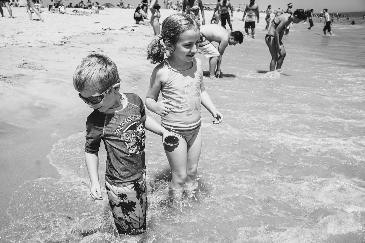 Two children wade through the water at the beach.