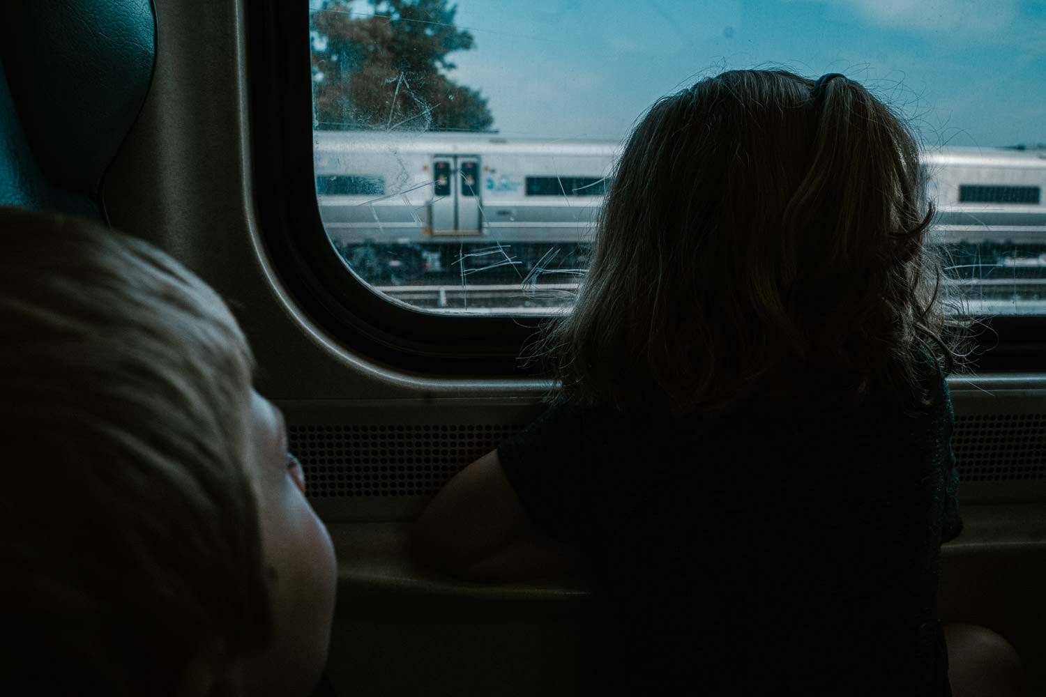 Two children look out a window of a train.
