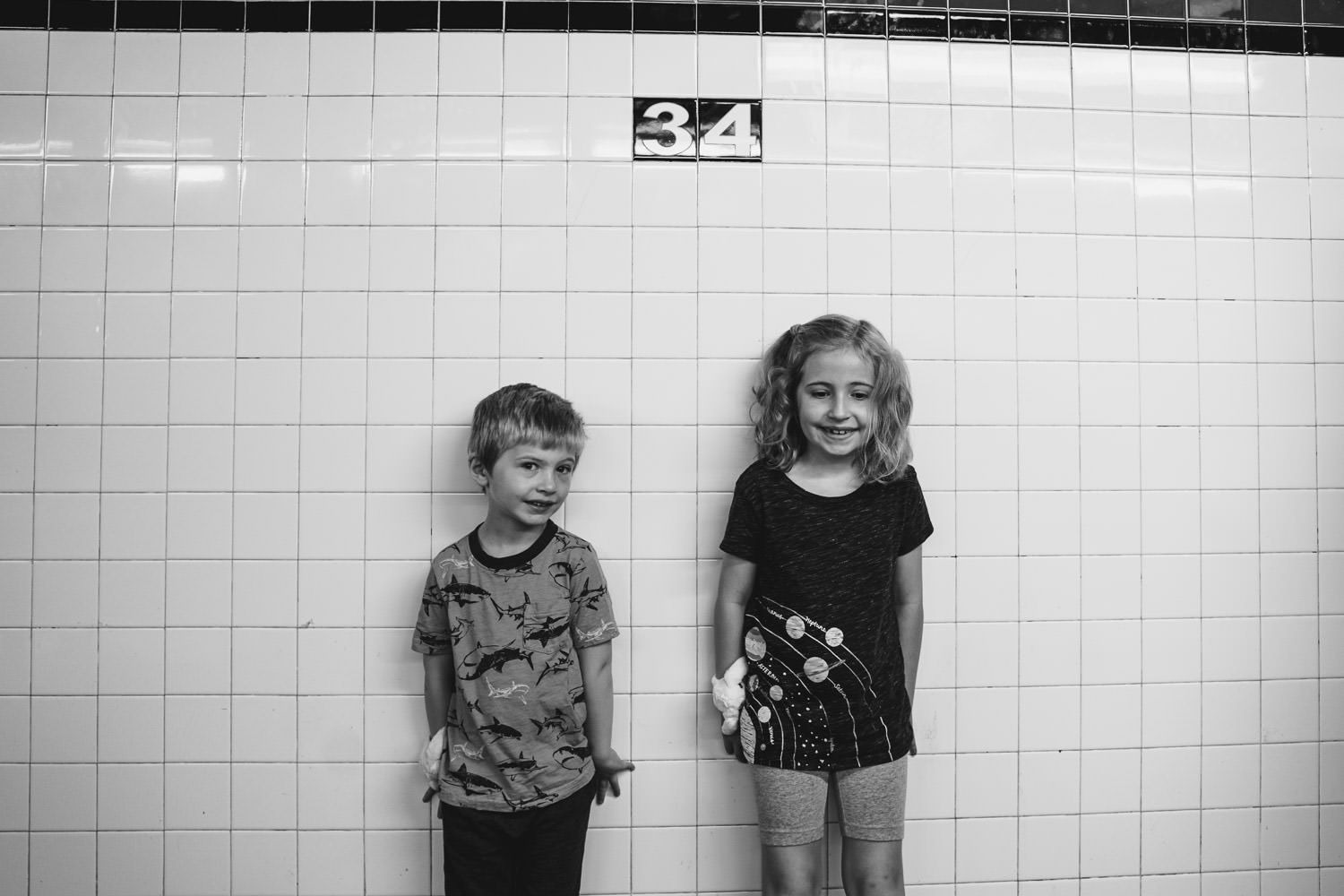 Two children stand on the subway platform.