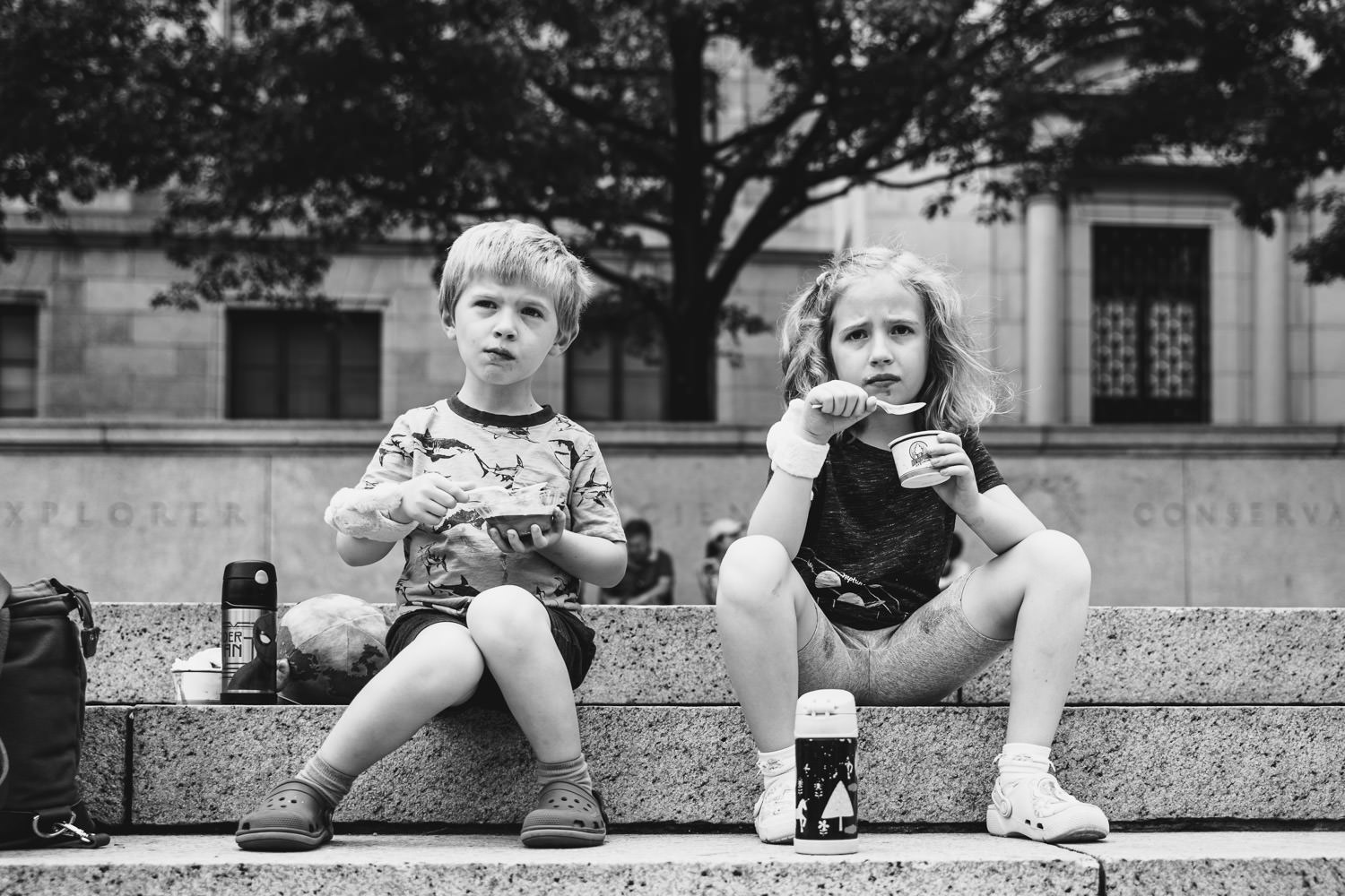 Two children eat ice cream on the steps of the Natural History Museum.