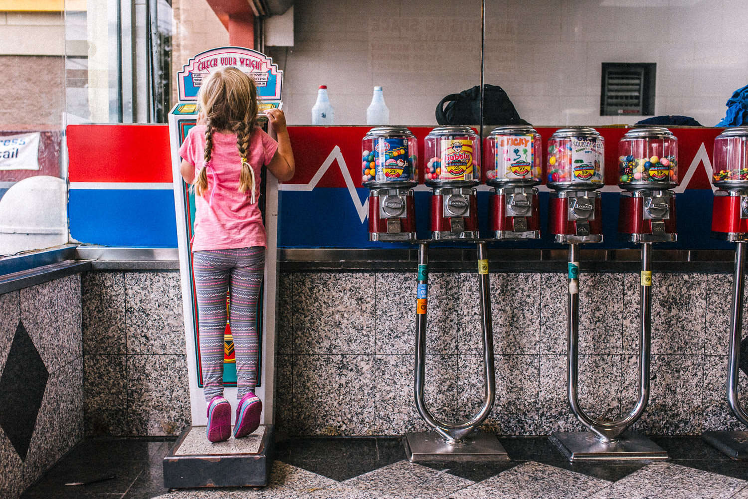 A little girl stands next to some gumball machines at the car wash.