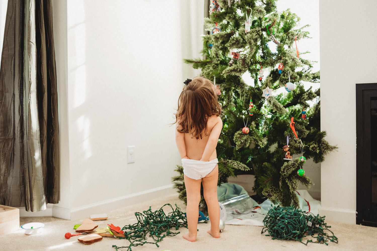 A little girl in her underwear stands in front of the Christmas tree.