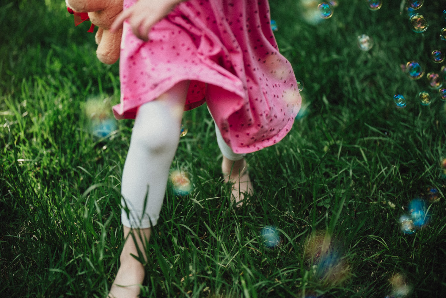 A little girl runs through some bubbles.
