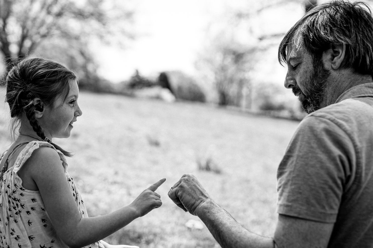 A father and daughter bump fists.