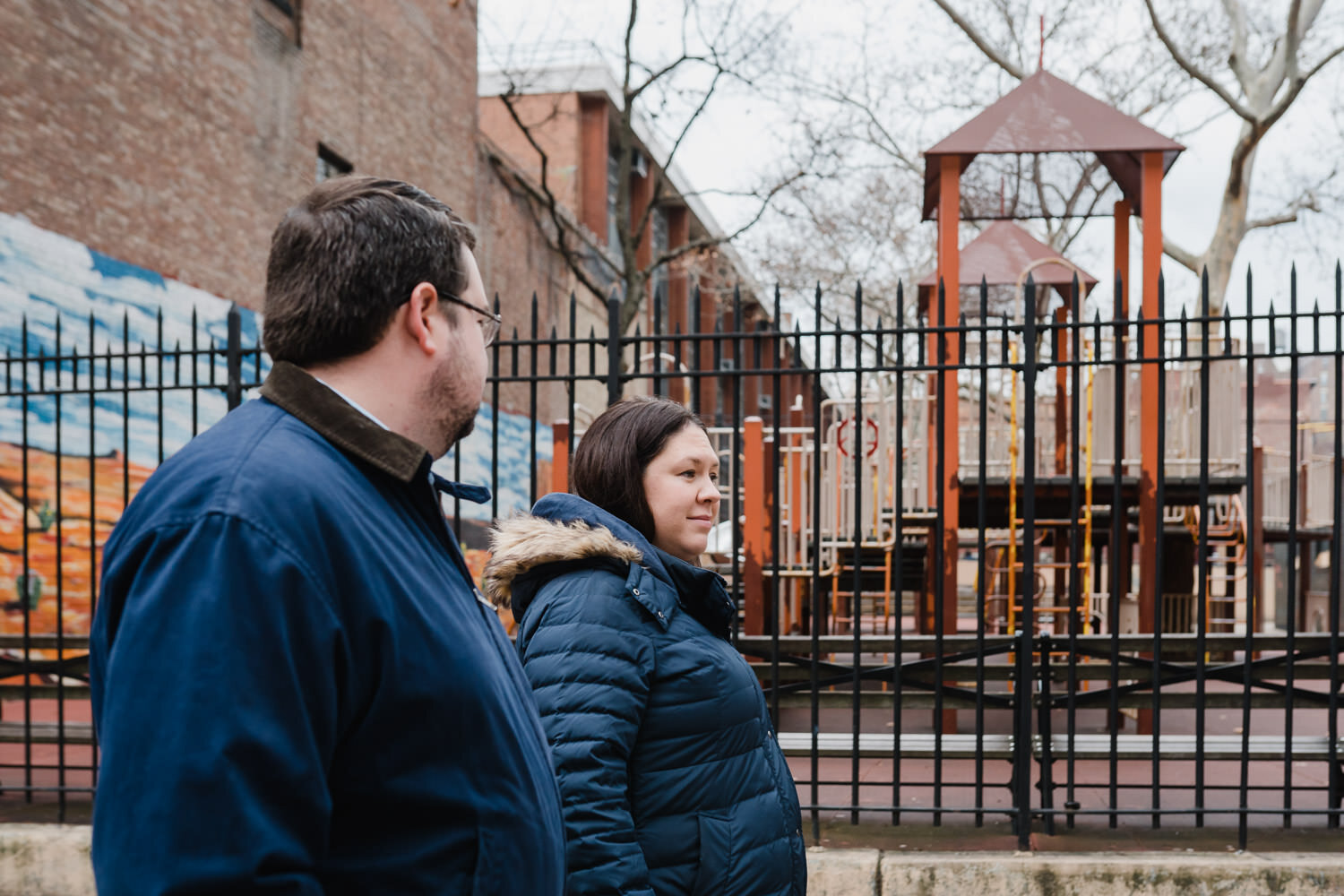 A couple walks by a playground on the upper west side.