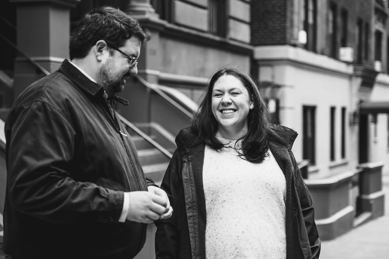 A couple smiles at each other on the street in Manhattan.