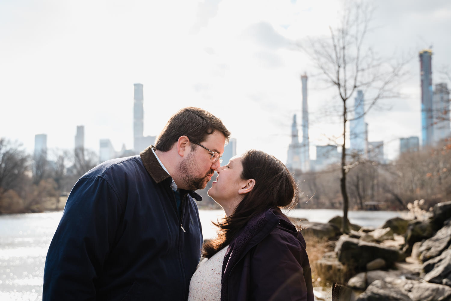 A couple kisses by the pond in Central Park.