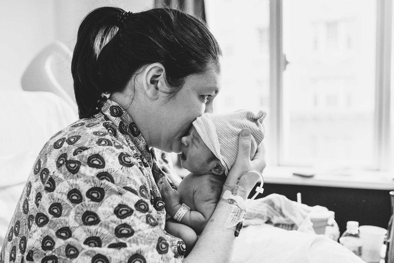 A mother kisses her newborn baby in her hospital bed.