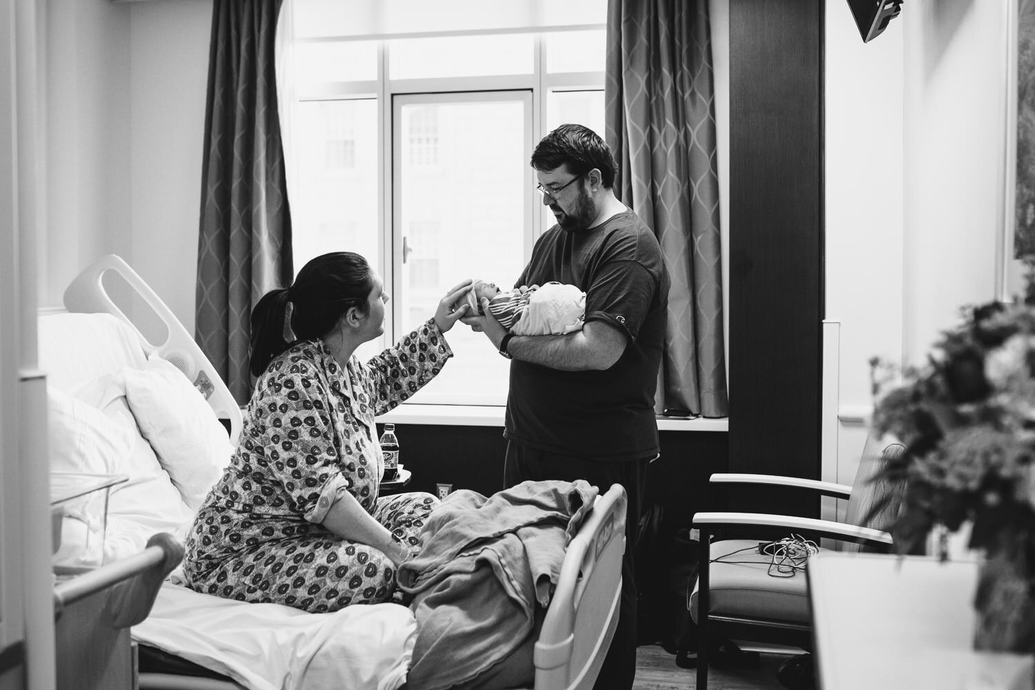 A couple and their newborn baby in their hospital room.