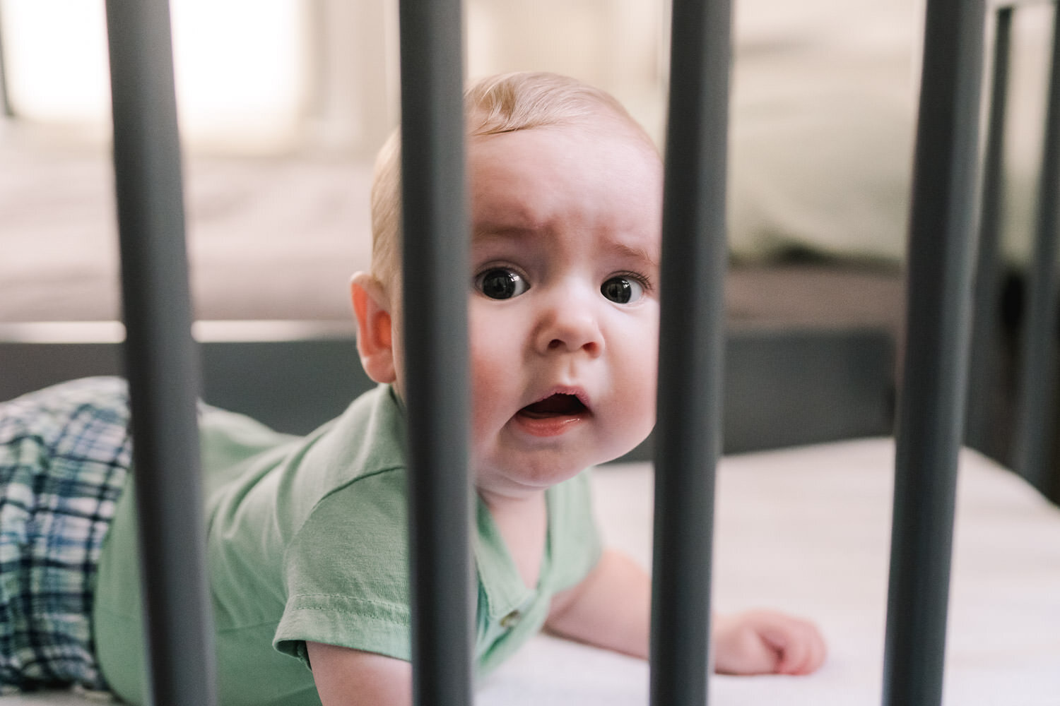 A baby peers through the slats of his crib.