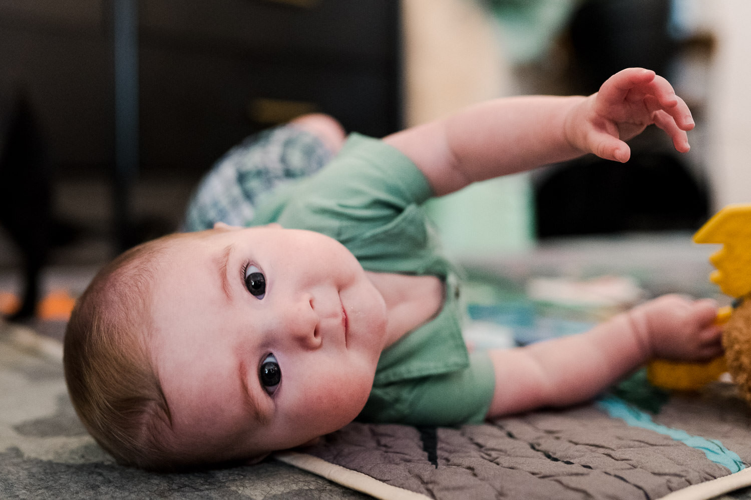 A baby rolls on his play mat.