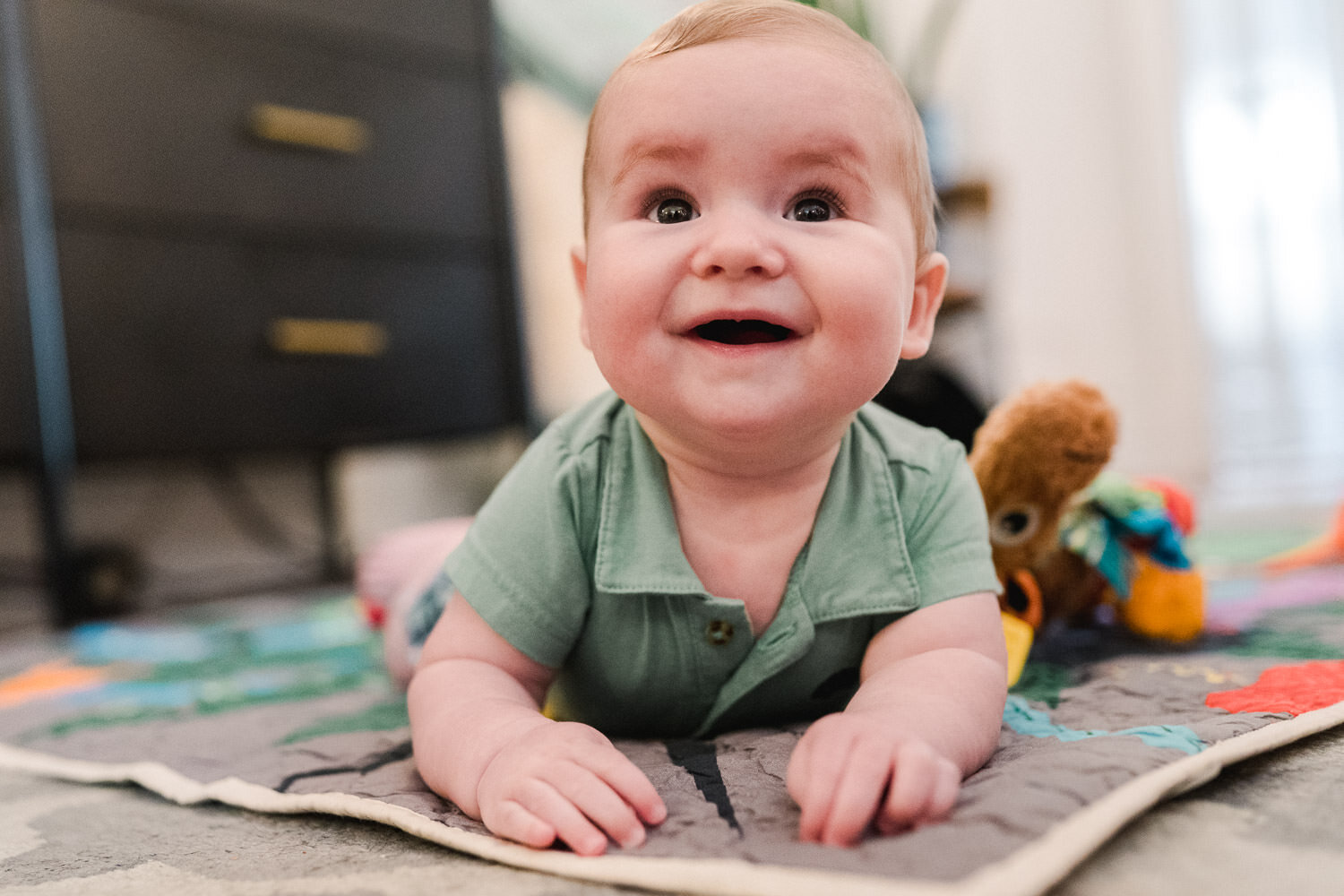 A baby smiles from his play mat.