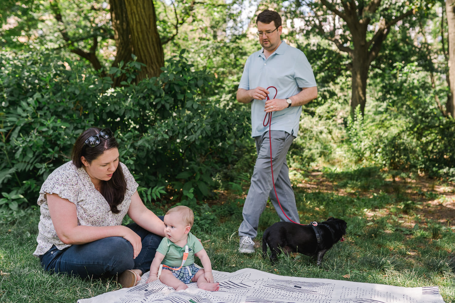 A family sits on a blanket in Central Park,