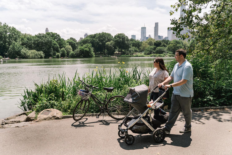 A couple push a stroller through Central Park.