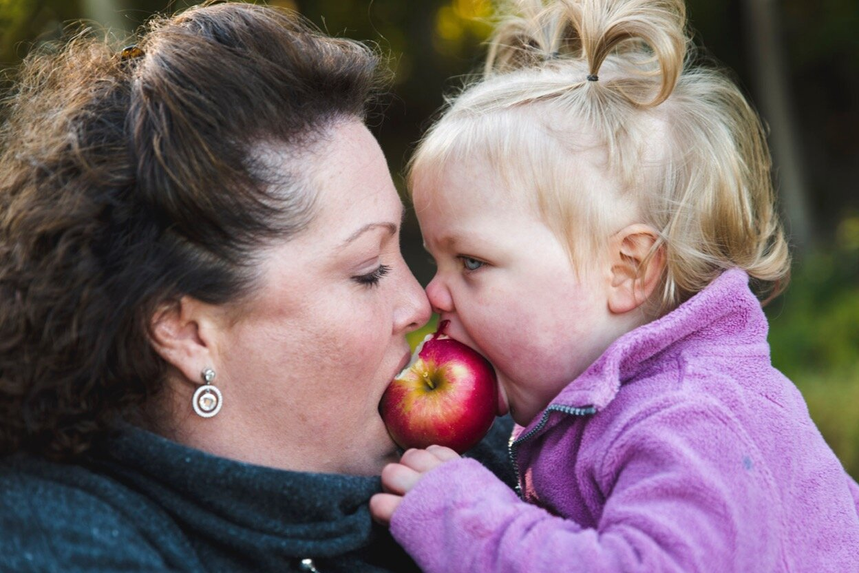 A woman and her toddler daughter share an apple.