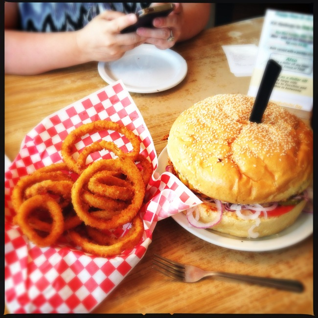"""The Pilot Butte Burger measures 9 inches across. This thing is HUGE. That is a 6"""" plate behind it by Carrie's hands."""