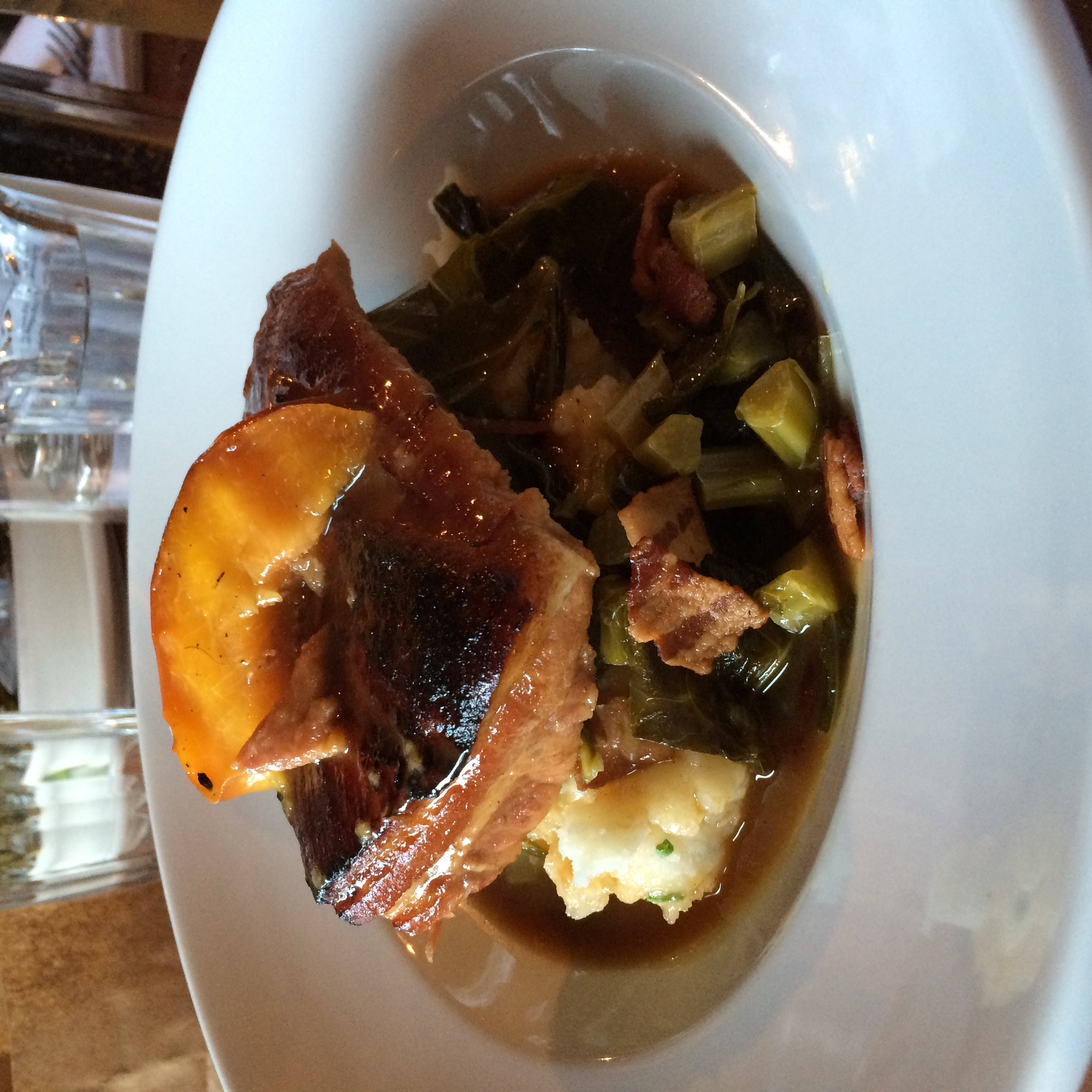 Cider-braised pork belly, bacon-braised collard greens, mash potatoes and a grilled apple