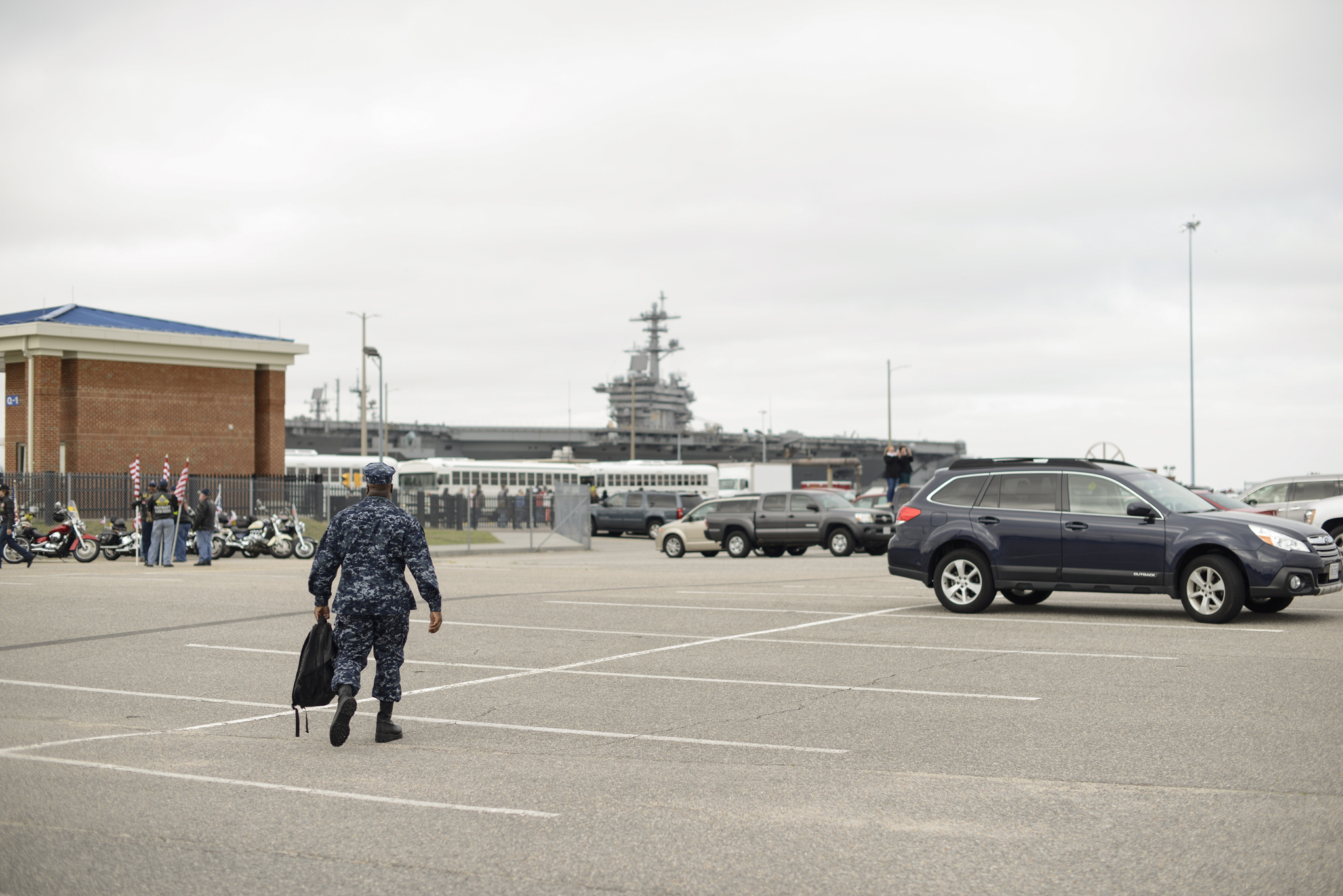 A solitary soldier walks towards his ship   USS Truman naval military homecoming   Maria Grace Photography