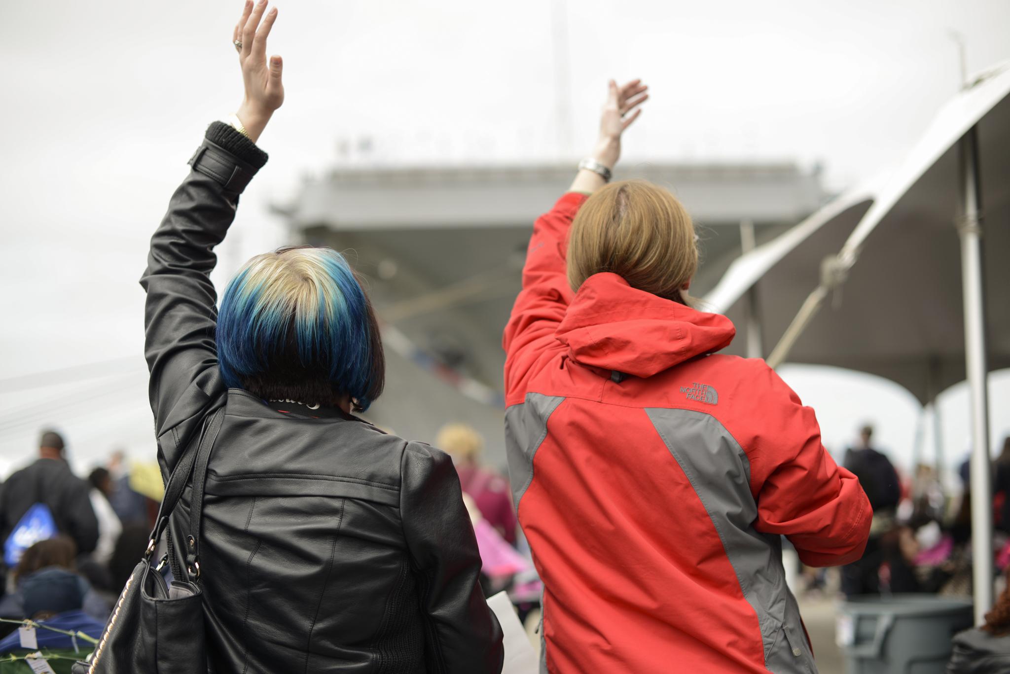 Wives waving at their men  USS Truman naval military homecoming   Maria Grace Photography