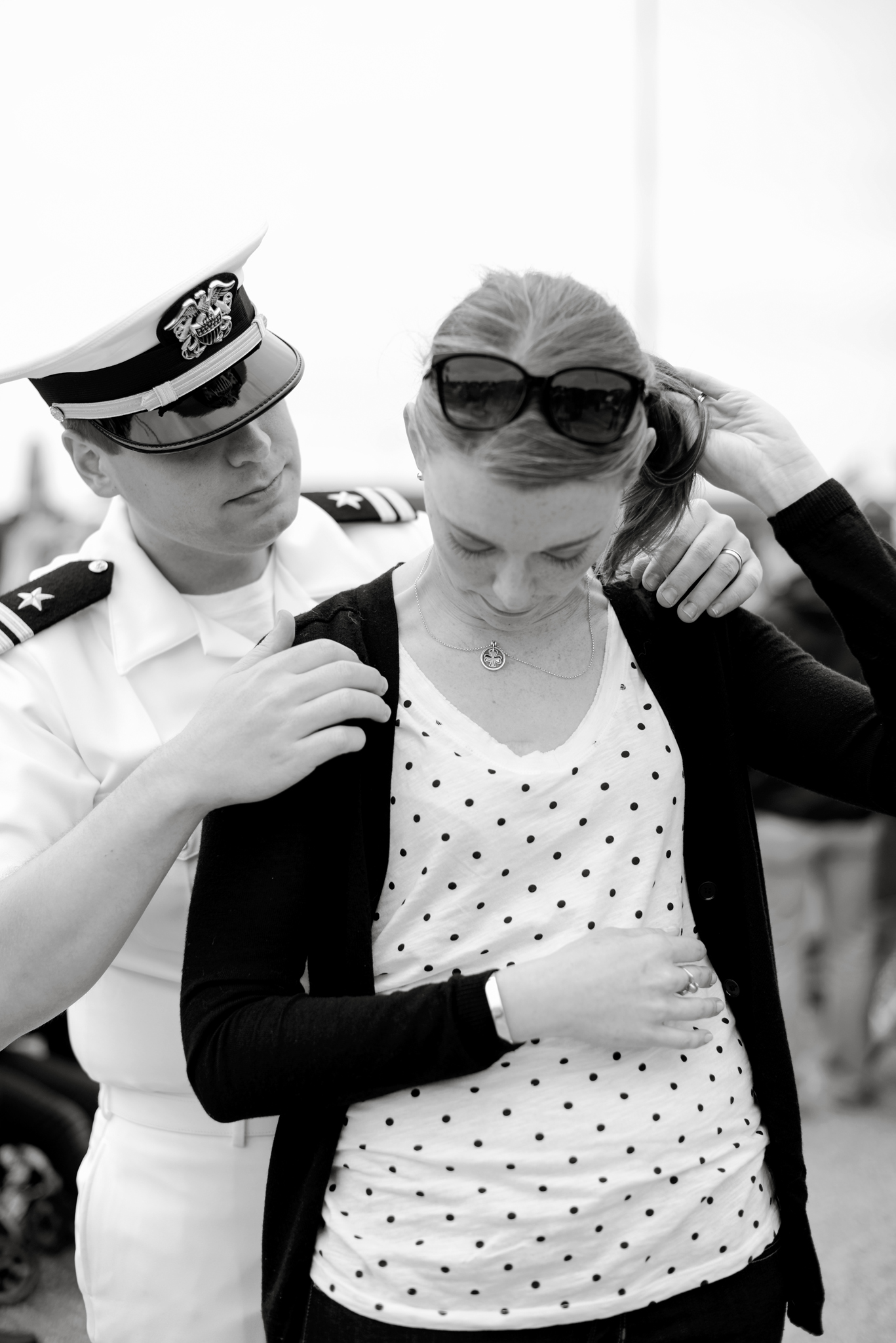 A husband helps his wife put on her shamrock necklace  USS Truman naval military homecoming   Maria Grace Photography