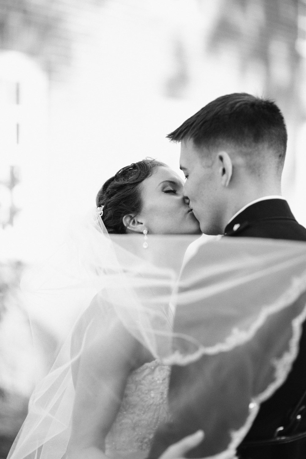 Bride and groom's kiss with windswept veil | Maria Grace Photography