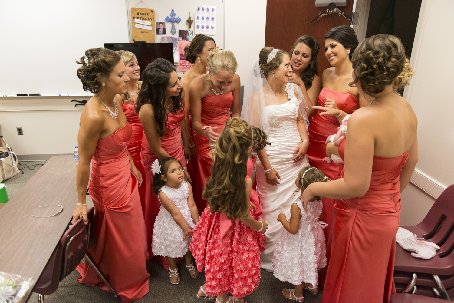 Bridesmaids helping bride get ready in bright coral dresses at Liberty Baptist Church