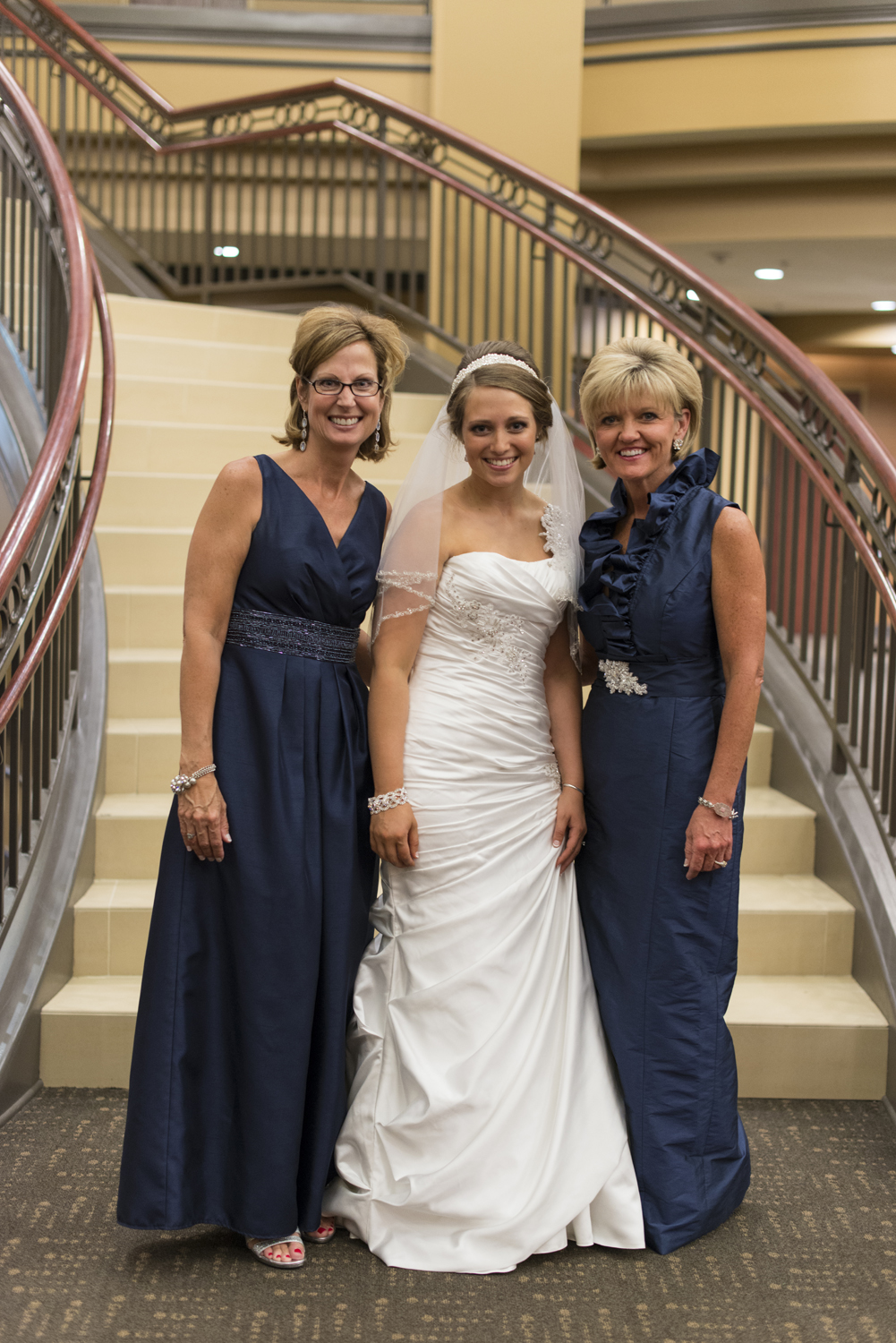 A bride with her mother and new mother-in-law before a wedding